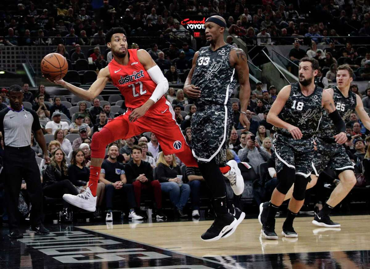 Washington Wizards forward Otto Porter Jr. (22) chases a loose ball past San Antonio Spurs forward Dante Cunningham (33) during the first half of an NBA basketball game in San Antonio, Sunday, Jan. 27, 2019. (AP Photo/Eric Gay)