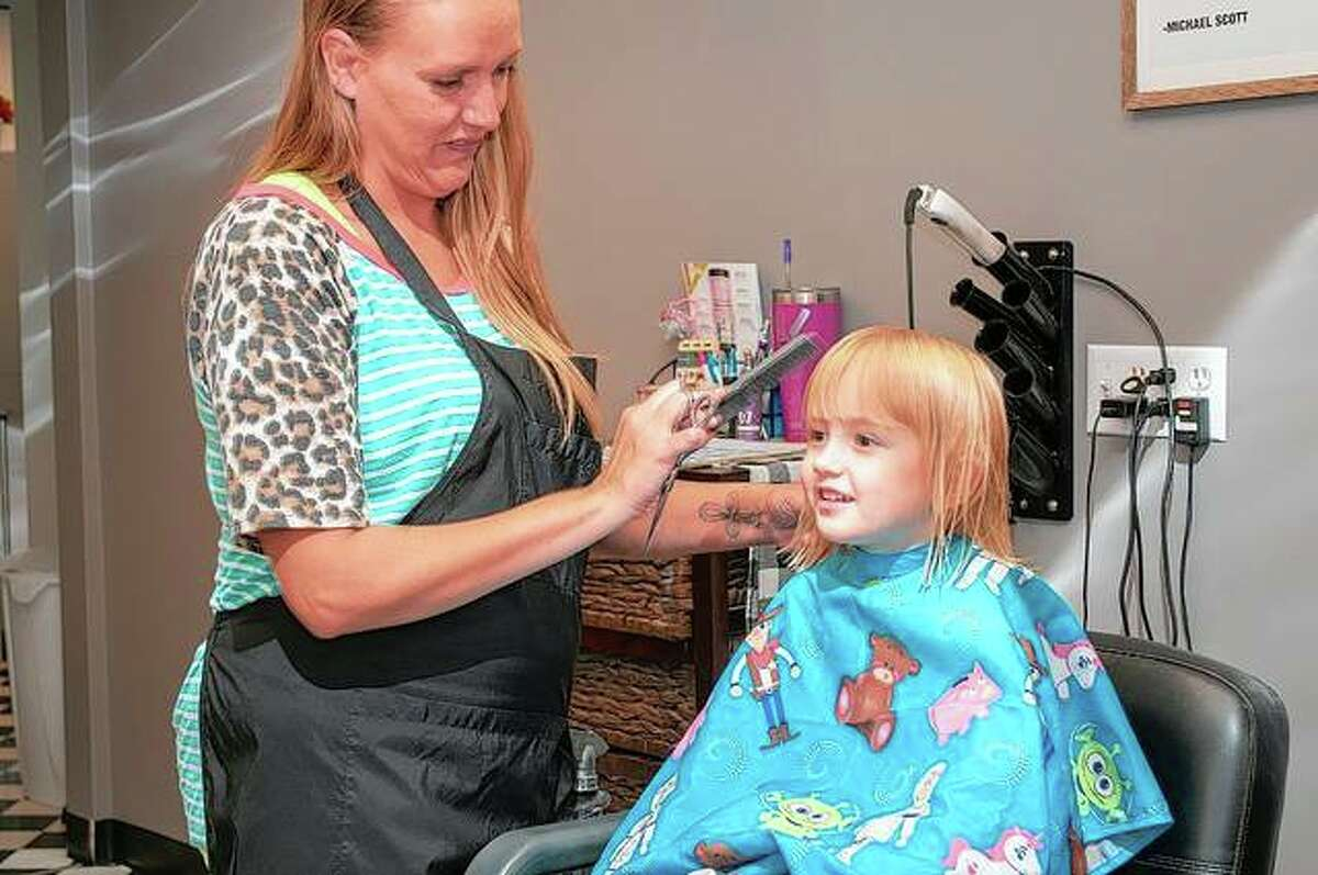 """Nickolas Spray, 3, gets the second """"official"""" haircut of his life by stylist Aubrey Reed at Shear Design in Jacksonville. His father said Nickolas has no problem getting his hair cut, even when it was done at home during the pandemic."""