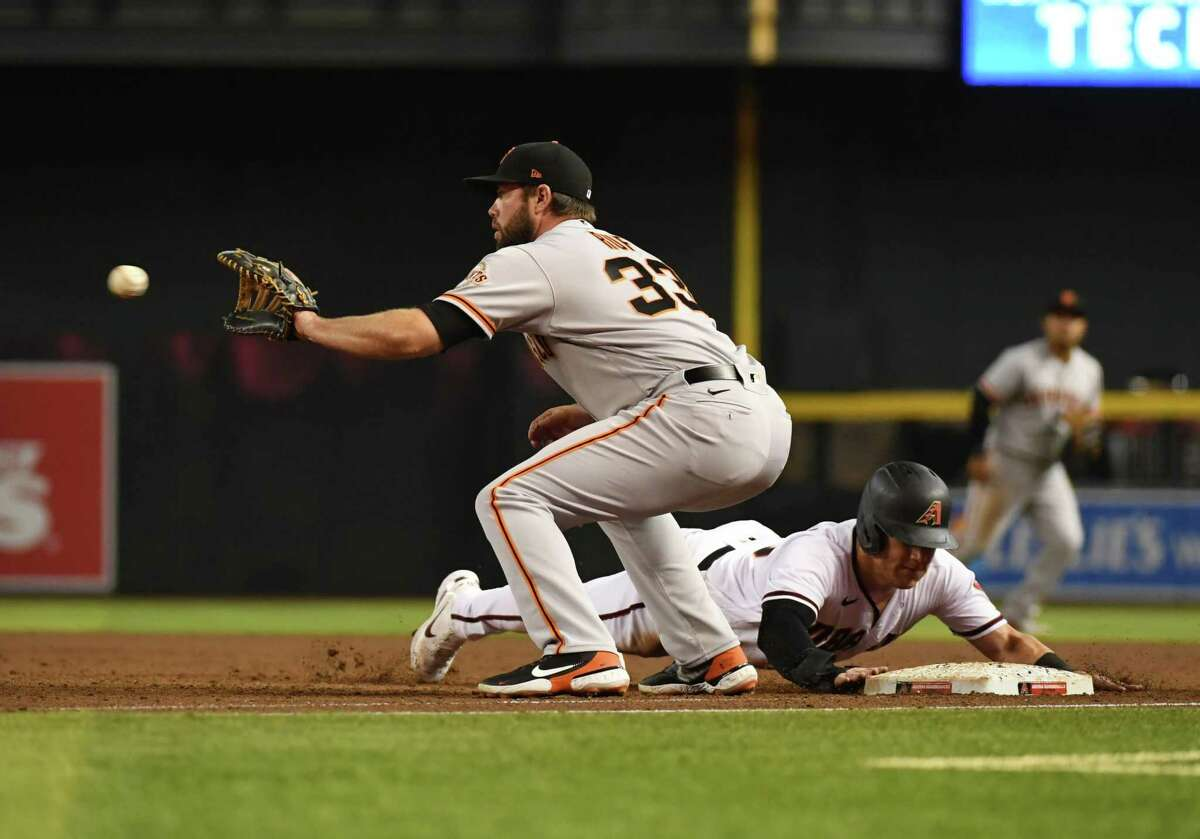 PHOENIX, ARIZONA - AUGUST 02: Kole Calhoun #56 of the Arizona Diamondbacks safely dives back to first base as Darin Ruf #33 of the San Francisco Giants waits on a throw from pitcher Anthony DeSclafain #26 during the third inning at Chase Field on August 02, 2021 in Phoenix, Arizona. (Photo by Norm Hall/Getty Images)