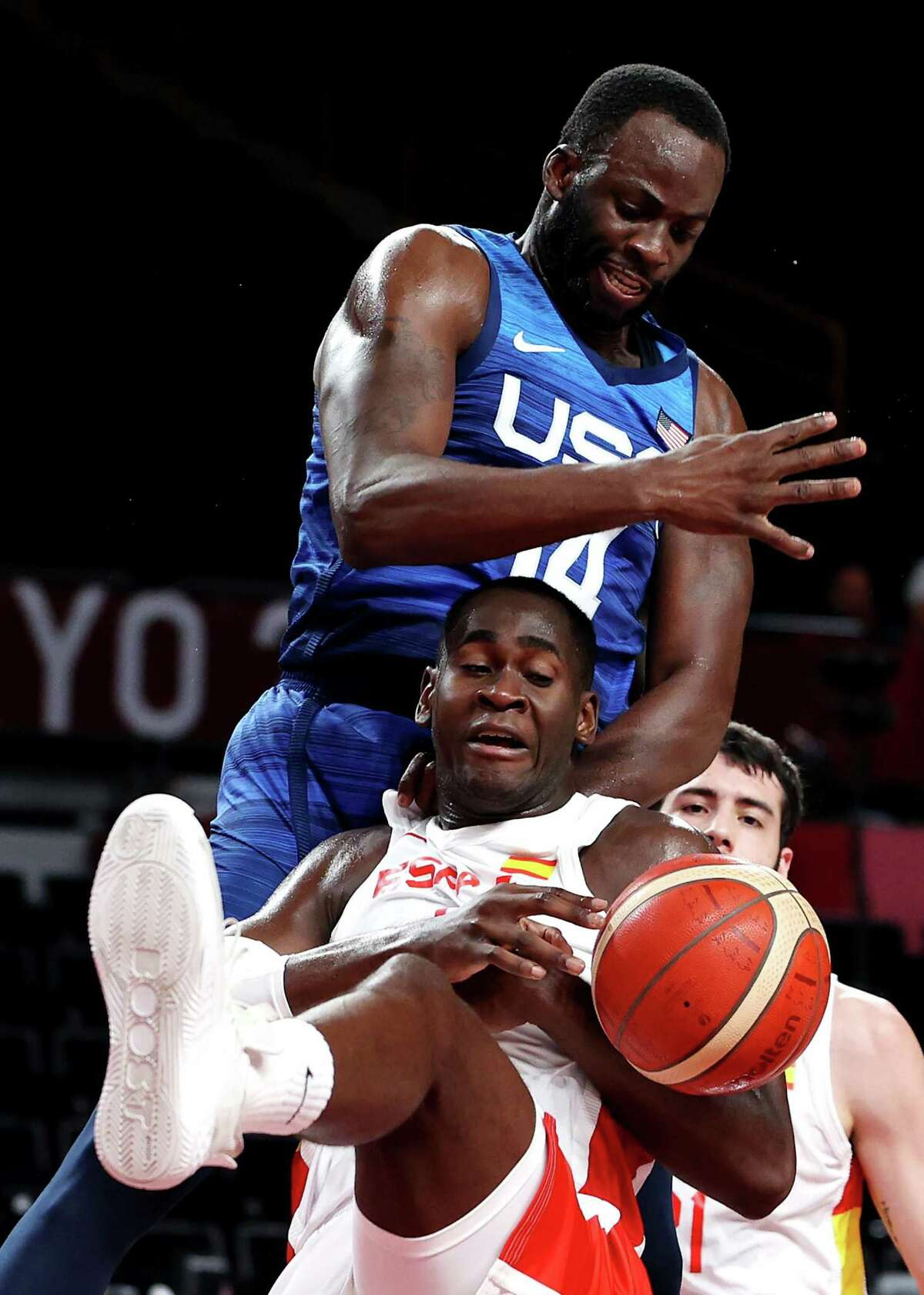 Draymond Green knocks the ball away from Spain's Usman Garuba during the second half of an Olympic quarterfinal basketball game. The Warriors' forward came off the bench to score four points, make two steals and collect a pair of assists.