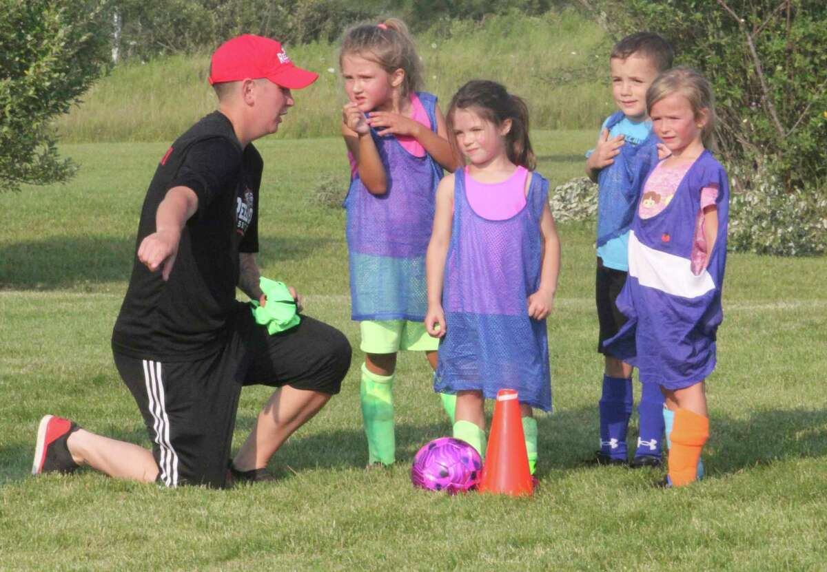 Reed City high school players (left) worked with youngsters during last week's soccer camp at the practice field. (Pioneer photo/John Raffel)