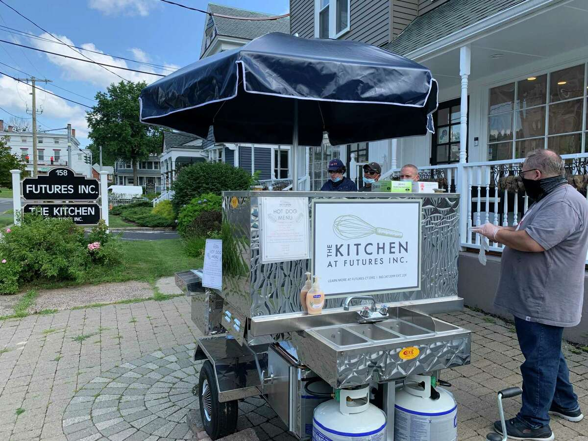Local nonprofit Futures Inc. recently opened this hot dog cart on Broad Street in Middletown to provide meaningful employment for individuals with disabilities. Ted Tabor and Wayne Stocking fill orders on Friday, July 30, 2021.