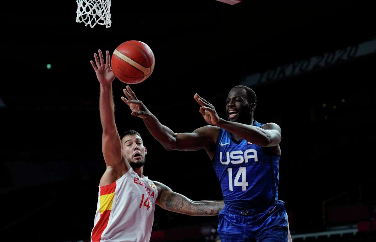 United States' Draymond Green (14), right, passes over Spain's Willy Hernangomez (14) during men's basketball quarterfinal game at the 2020 Summer Olympics, Tuesday, Aug. 3, 2021, in Saitama, Japan.