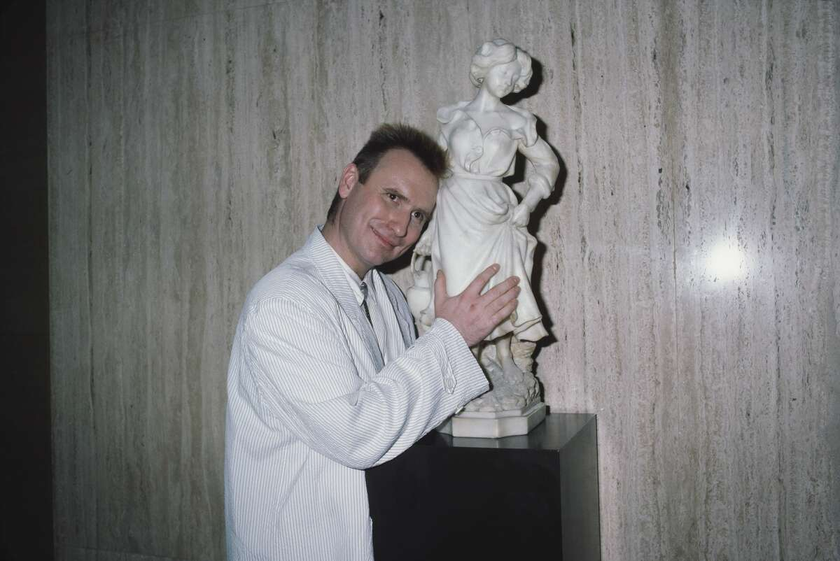 British-Australian singer-songwriter and musician Colin Hay, frontman with Men at Work, poses beside a statuette of a woman at the 5th Annual American Video Awards, held at the Scottish Rite Auditorium in Los Angeles, California, 26th February 1987.