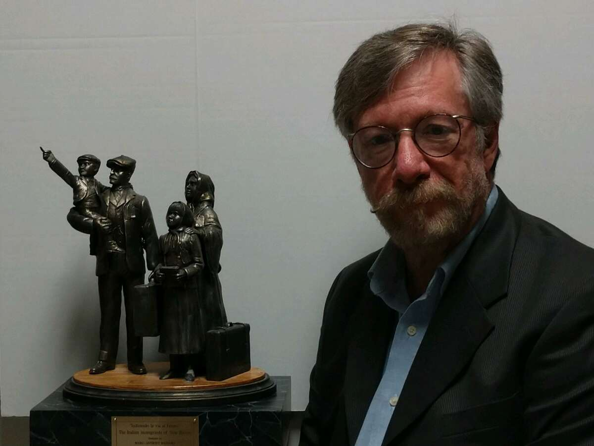 """Branford sculptor Marc-Anthony Massaro, whose grandfather was an Italian immigrant who settled in New Haven's Wooster Square neighborhood, poses in July 2021 with a one-sixth-scale model of his design, entitled, """"Indicando la via al futuro,"""" which the Wooster Square Monument Committee chose to replace the Christopher Columbus statue that was removed from Wooster Square in 2020."""
