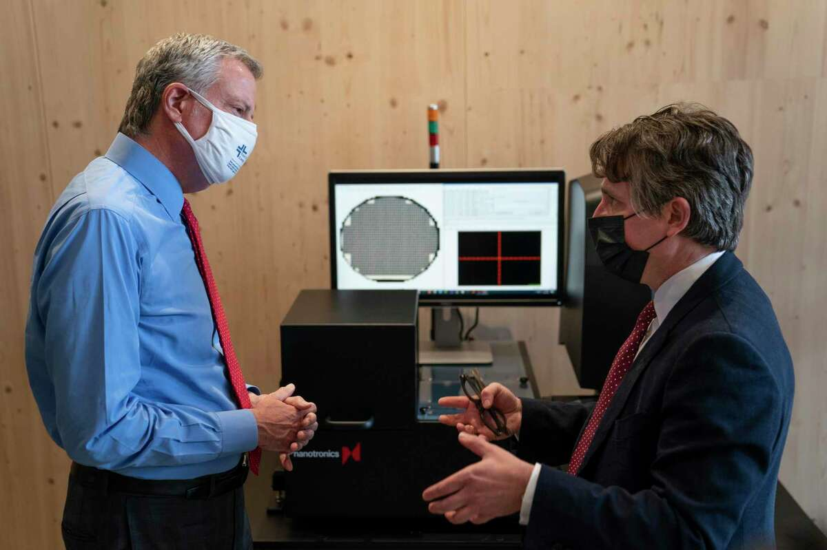 New York Mayor Bill de Blasio, left, speaks with Matthew Putman, co-founder and CEO of Nanotronics. De Blasio will announce Tuesday that city residents will have to show proof that they've received a COVID-19 vaccination before gaining entry into restaurants, fitness centers and other venues.