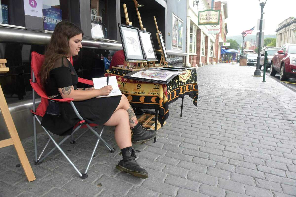 Artist Lacee Yurtoglu sketches while sitting with her work during a past Art Walk in New Milford.