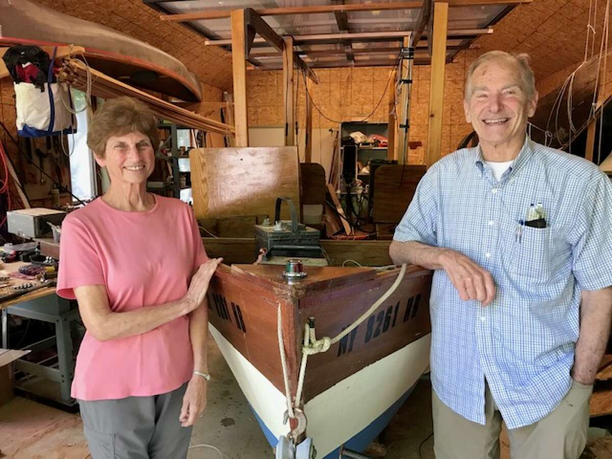 Harriet and David Borton stand by a prototype solar boat in a garage-turned-workshop in Brunswick.