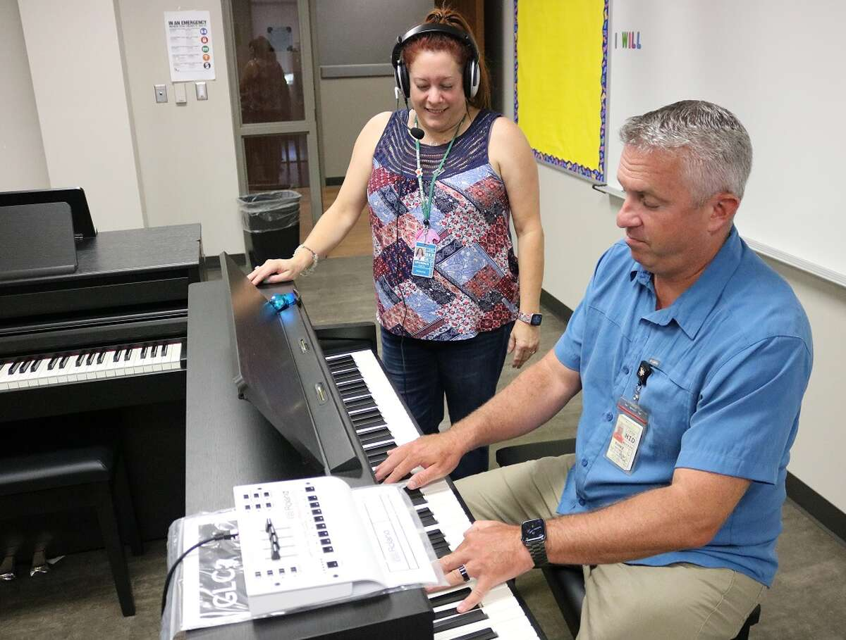 Matthew Burke, La Porte ISD's director of performing and visual arts, demonstrates to Sixth Grade Campus Principal Alicia Upchurch how a teacher can play music on a new digital piano while teaching students listening with headphones at their assigned pianos. The teacher also will have the ability to listen to individual students as the entire class practices.