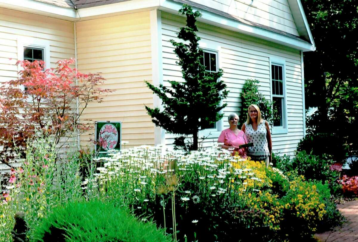 Mary Metzger, of the Spirit of the Woods Garden Club Inc, presents Eileen Postma (right) with the July Garden of the Month award. (Courtesy photo)