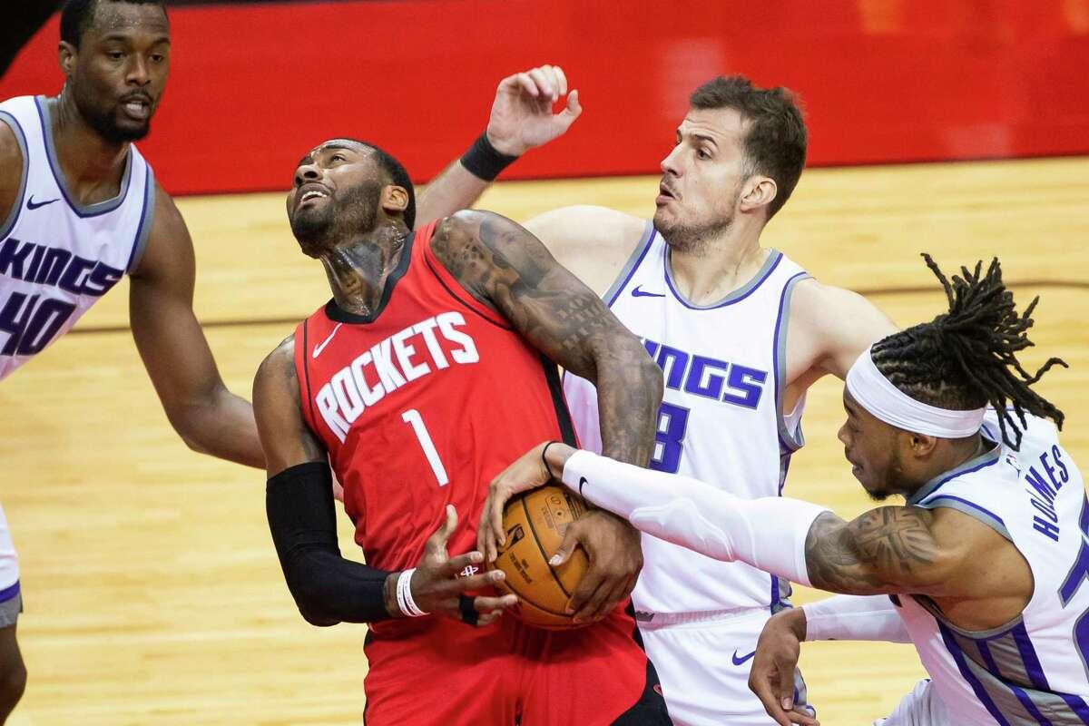 Houston Rockets guard John Wall (1) drives past Sacramento Kings forward Richaun Holmes (22) and forward Nemanja Bjelica (8) during the third quarter of an NBA game between the Houston Rockets and Sacramento Kings on Saturday, Jan. 2, 2021, at Toyota Center in Houston.