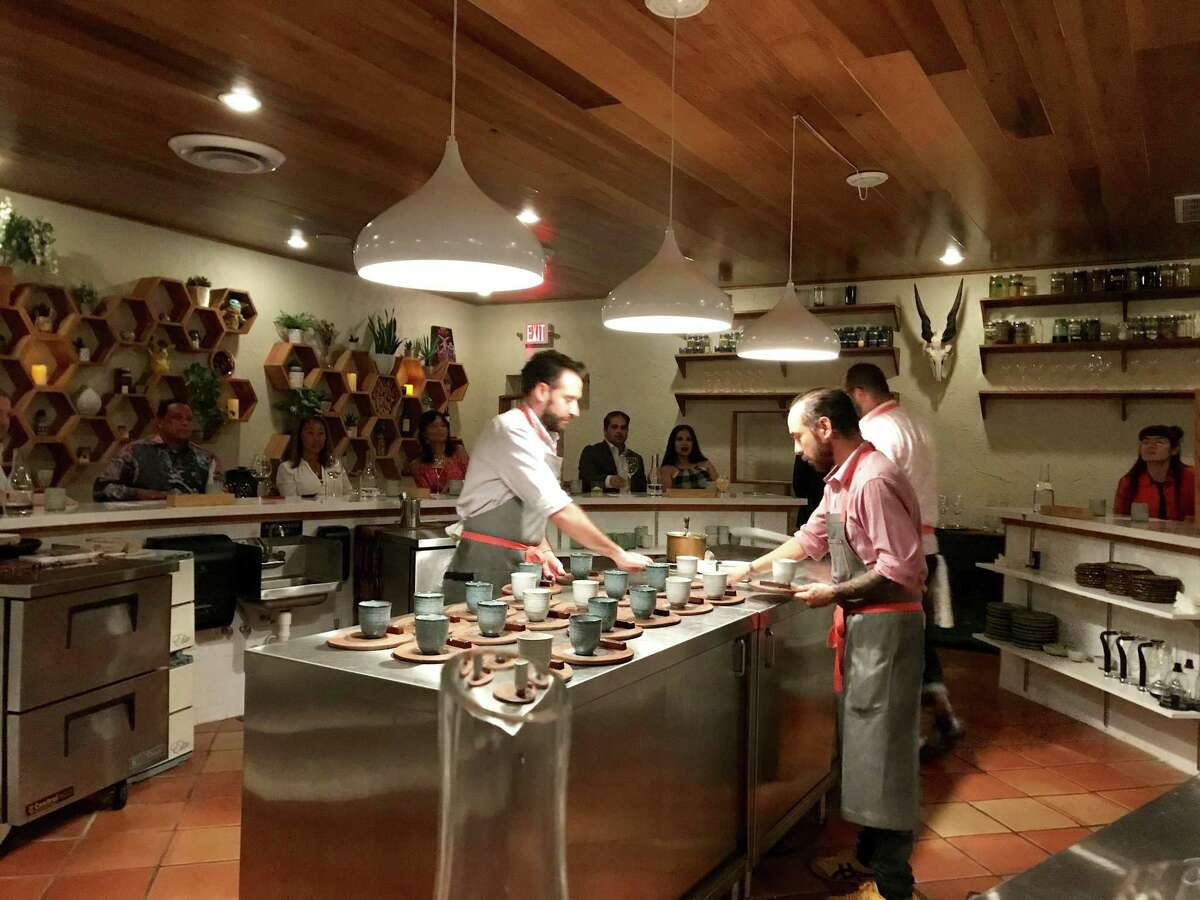 Chef Brandon Silva, right, and sous chef Javier Becerra work in the open kitchen that anchors the dining room at Degust in Spring Branch.