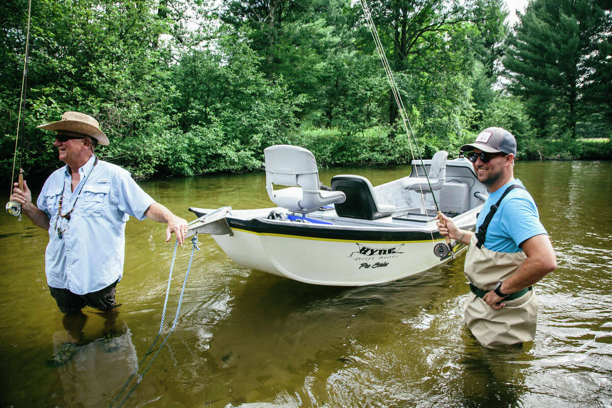 Two men are pictured fly fishing on the Pere Marquette River.
