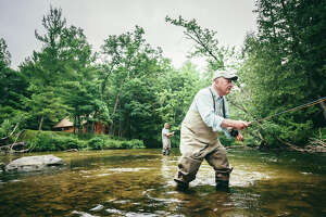Pictured is a man fly fishing.