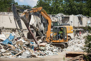 Demolition continues on the former Holiday Inn on Wackerly Street in Midland on Tuesday, Aug. 3, 2021, one day after its owner was handcuffed and sent to jail for failing to comply with demolition orders and not paying fines. (Katy Kildee/kkildee@mdn.net)