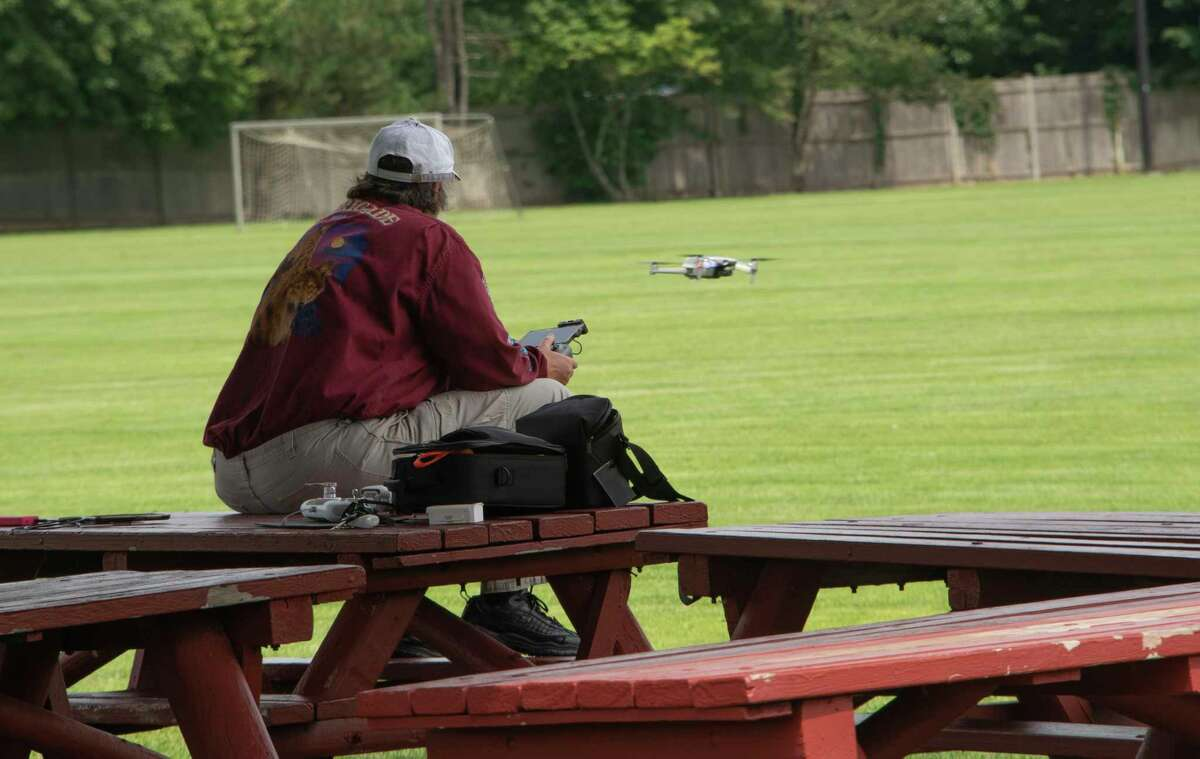A person sits on a picnic table in a pavilion and operates a drone near the soccer fields at Clifton Commons on Tuesday, Aug. 3, 2021 in Troy N.Y.