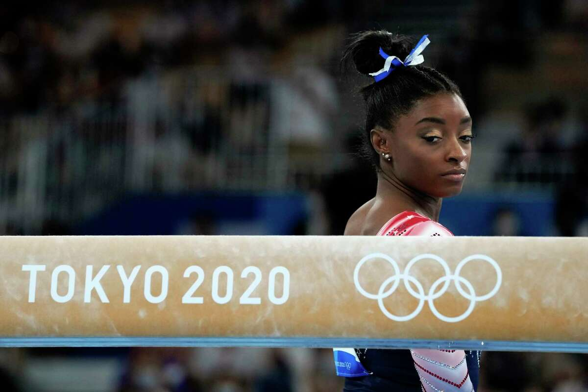 Simone Biles prepares to start her performance on the balance beam during the artistic gymnastics women's apparatus final at the 2020 Summer Olympics.