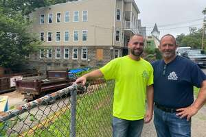 Don Stanziale Jr., and his son, Don III, owners of Midland Development & Contracting, in front of Coram Avenue properties — one they are renovating, the other a vacant lot that could soon become apartments.