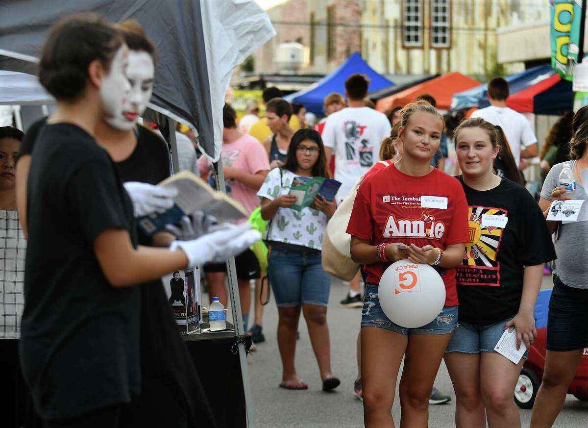 """This year's Tomball Night is Aug. 6, 2021. Shown here: Delaney Nations, center, and Miranda York, right, both Tomball High School seniors and members of The Tomball Stage, check out the pantomime group """"One Mind"""", from the church ITDA and Potter's Workshop, left, while handing out brochures publicizing the THS Theatre Dept.'s 2019-2020 season schedule during Tomball Night on August 2, 2019."""