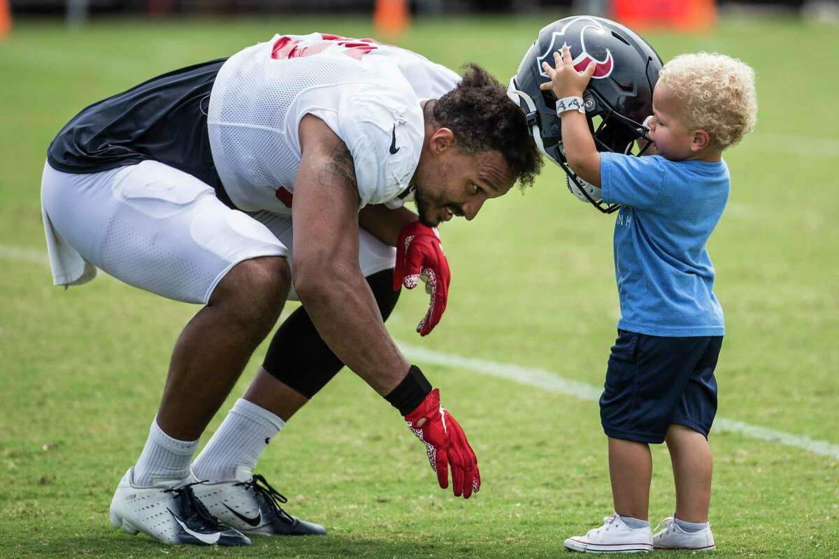 Houston Texans defensive end Derek Rivers (95) bends down as his son, Luke, puts his helmet on his head during an NFL training camp football practice Tuesday, Aug. 3, 2021, in Houston.