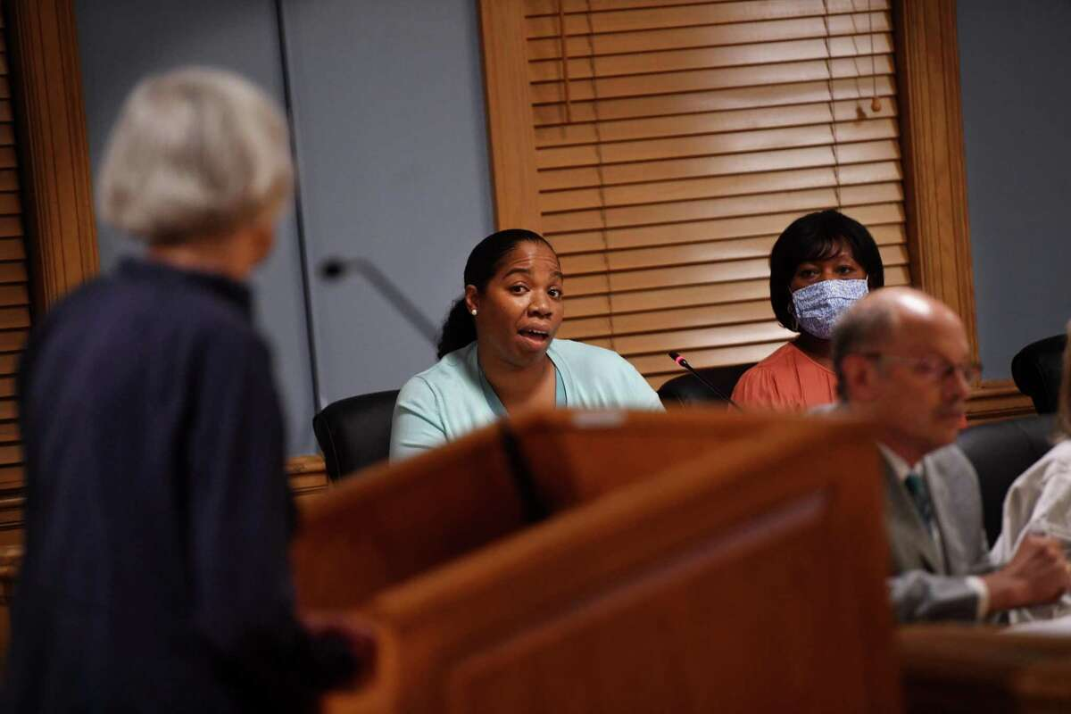 Town Council member Joy Colon, center, addresses Jeannine Stauder, left, a new member of the town's Diversity and Inclusion Task Force, during the council meeting at Town Hall in Trumbull, Conn. on Monday, August 2, 2021.