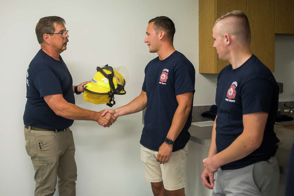 """Jerome Township Fire Chief Jerry """"Jake"""" Cole, left, shakes hands with Jackson Carmoney, center, as he is presented with his new helmet in honor of the completion of his training through the Jerome Township Fire Academy, Monday, Aug. 2, 2021 at the Jerome Township Fire Department in Sanford. (Katy Kildee/kkildee@mdn.net)"""