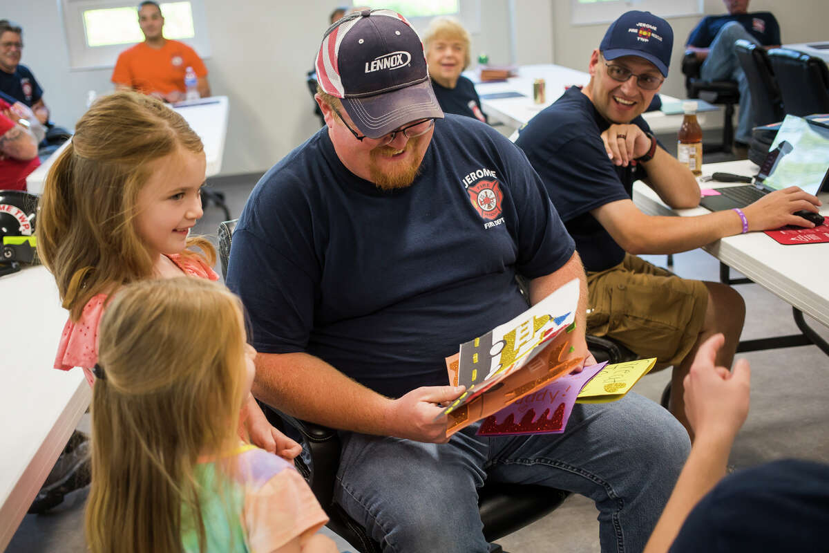 New Jerome Township firefighter John Ziems, center, receives cards of congratulations from his daughters, Huntington, 7, left, and Paislee, 4, bottom left, Monday, Aug. 2, 2021 at the Jerome Township Fire Department in Sanford. (Katy Kildee/kkildee@mdn.net)