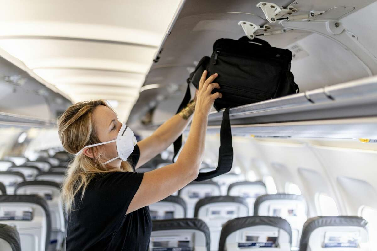 Female passenger is wearing an FFP 3 face mask while putting luggage in lockers on plane.
