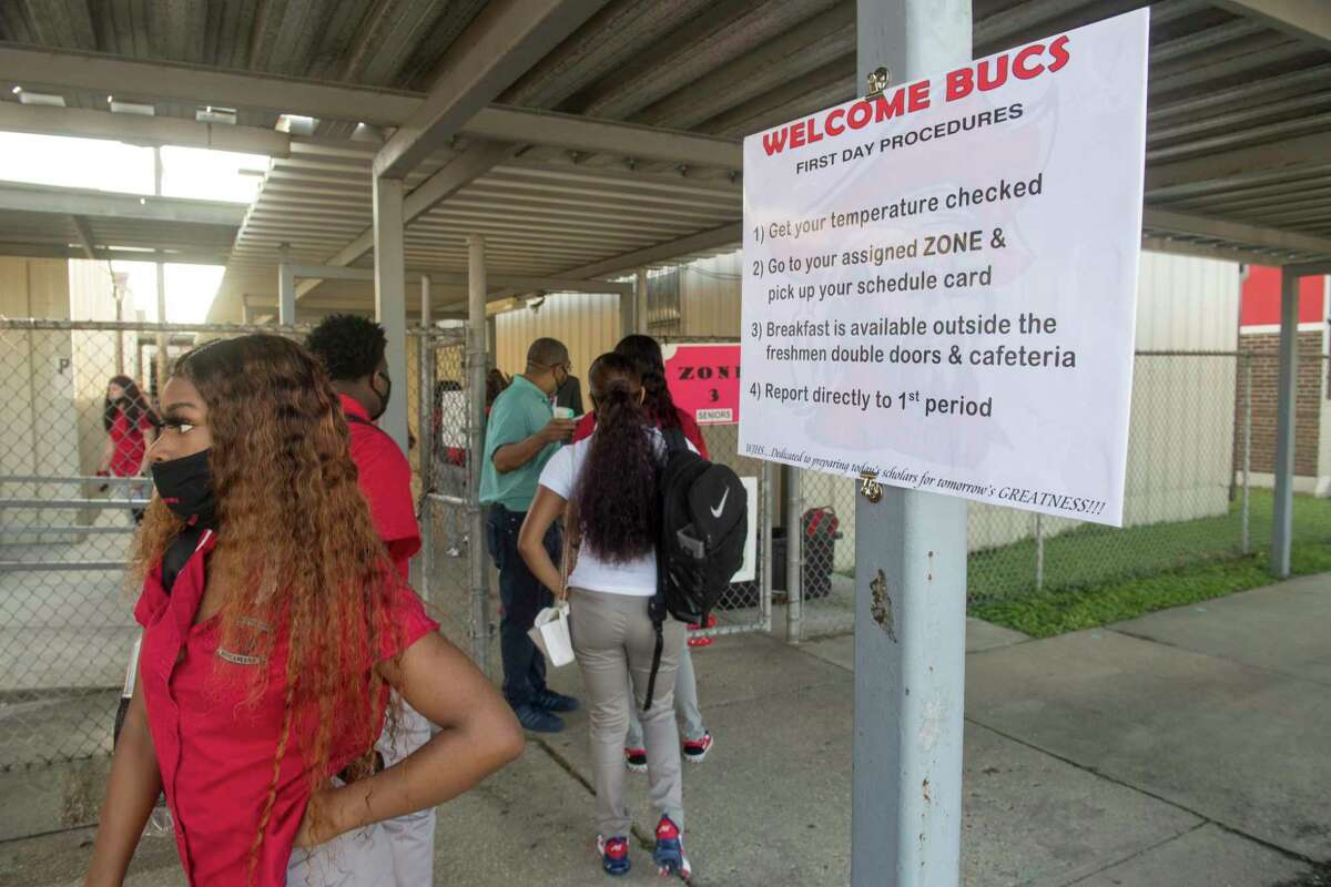 In this Aug. 31, 2020, photo, a sign in front of West Jefferson High School in Harvey, La., explains what returning students need to do to stay safe during the coronavirus pandemic. Despite climbing numbers of COVID-19 cases around Louisiana, state education leaders are leaving decisions on mask mandates, physical distancing and other measures aimed at lessening coronavirus spread to local public school districts for the upcoming year.