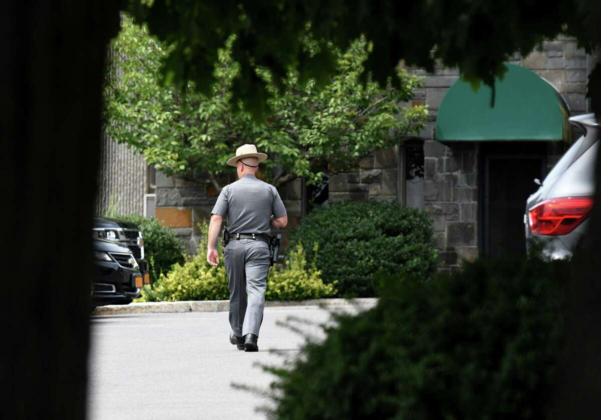 """A New York State trooper stationed at the Executive Mansion walks back from the entryway guard shack on Tuesday, Aug. 3, 2021, in Albany N.Y. State Attorney General Letitia James announced that her office's five-month investigation ?""""has concluded that Gov. Andrew M. Cuomo sexually harassed multiple women and in doing so violated federal and state law.?•"""