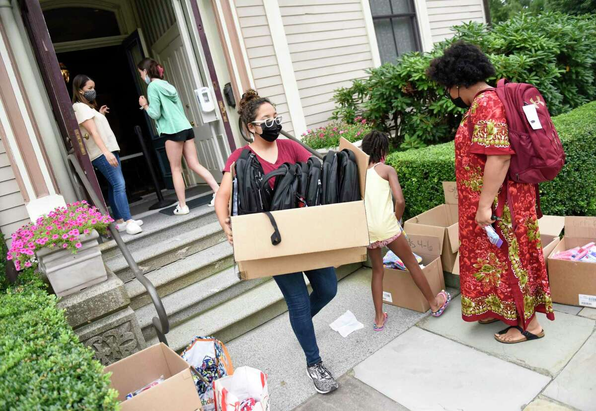 Neighbor to Neighbor volunteer Dilailah Ruiz, 14, distributes backpacks to students for the upcoming school year at the Tomes Higgins House on the Christ Church campus in Greenwich, Conn. Tuesday, Aug. 3, 2021. About 450 backpacks were distributed to elementary through high school students. Each backpack contained essential supplies including a binder, notebooks, folders, pens and pencils, as well as crayons for elementary students.