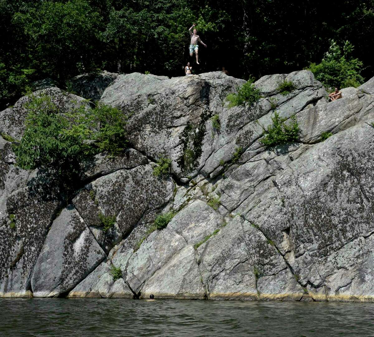 Local teenagers jump from the cliffs in Richardson Park into Mamanasco Lake. The Mamanasco Lake Improvement Fund (MLIF) is celebrating its 50th anniversary this year. Friday, July 30, 2021, in Ridgefield, Conn.