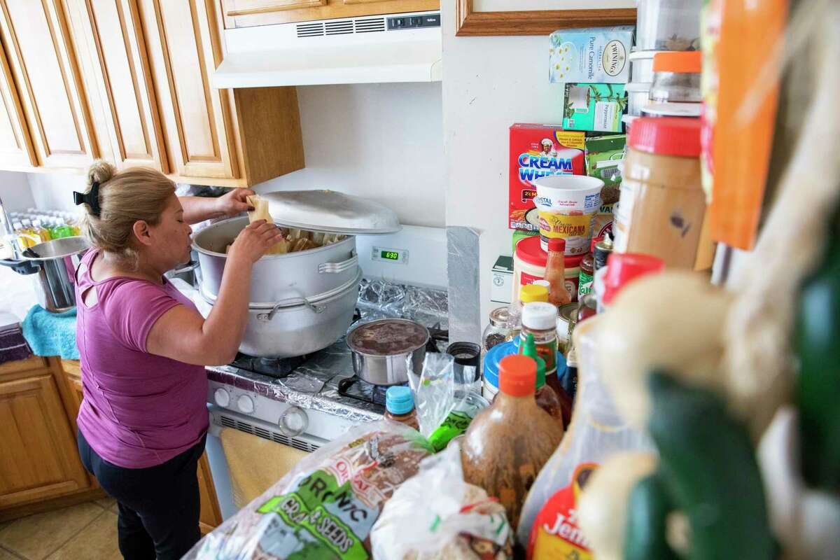 Victoria Medina prepares tamales in the one-bedroom Mission District apartment she shares with her three children. Lately, she says more people in the neighborhood are selling food to make ends meet.