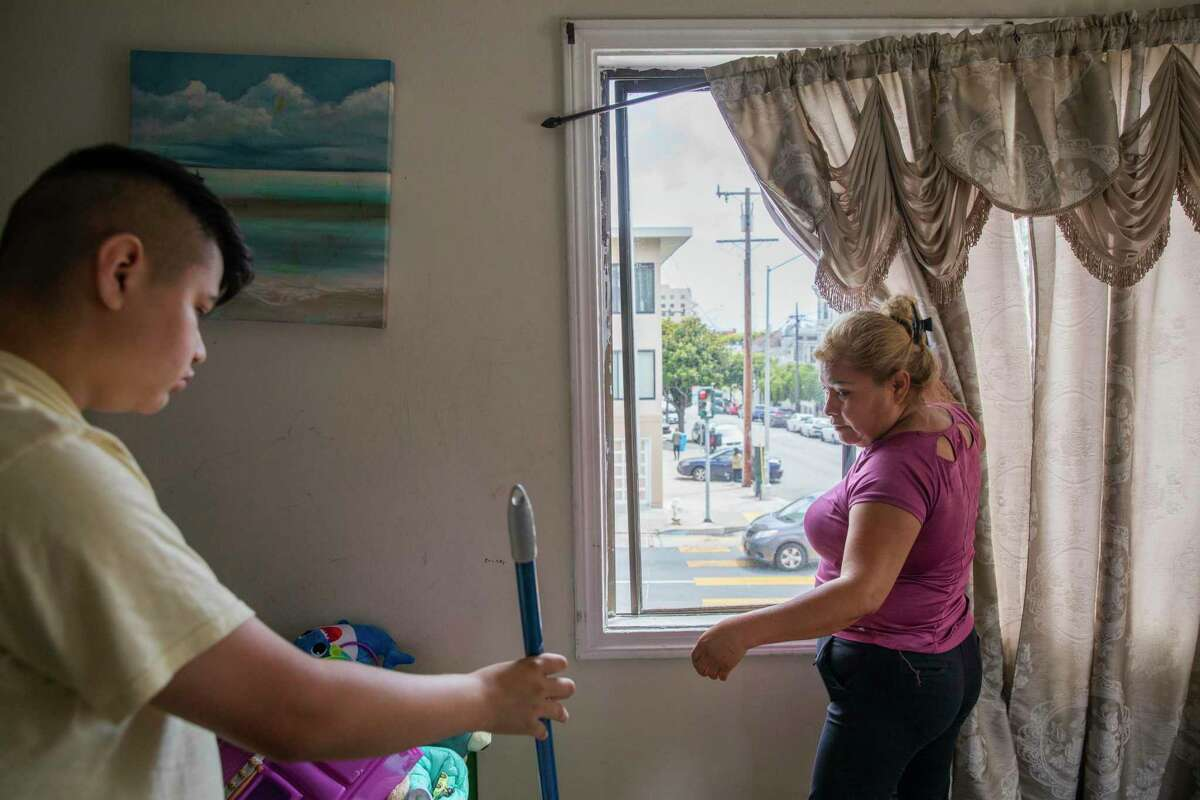 From left: Alan Lopez, 13, helps her mother Victoria Medina clean their San Francisco apartment. Medina is hoping state or local rent relief programs will help her family stay in their longtime home.