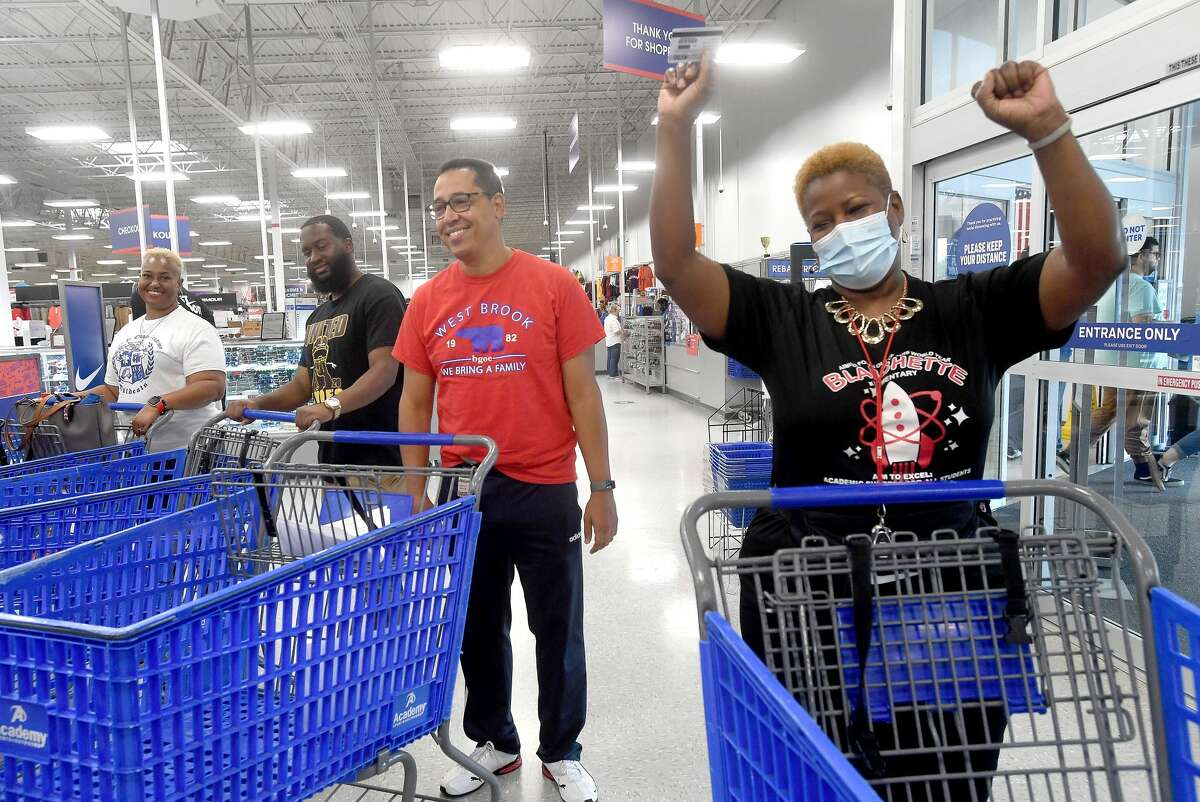 From left, Odom Academy's Tamieka Patterson, Beaumont United's Chevon Martin, West Brook's Jose Rendon and Blanchette's Elizabeth Ned-Broussard cheer as they are offered their gift cards during a Teacher Appreciation give-away Tuesday at the Beaumont store. Four BISD PE teachers and coaches were awarded $500 gift cards, which actually translated to $550 with their 10% teacher discount. Photo made Tuesday, August 3, 2021 Kim Brent/The Enterprise