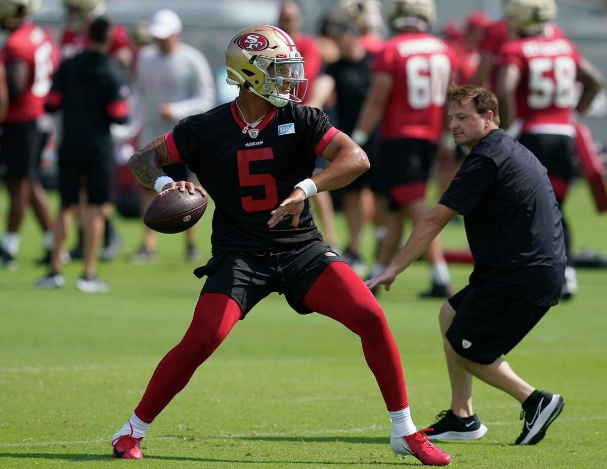 Trey Lance throws a pass in front of 49ers quarterbacks coach Rich Scangarello at training camp in Santa Clara. The rookie quarterback took his first snap of camp with the first team.