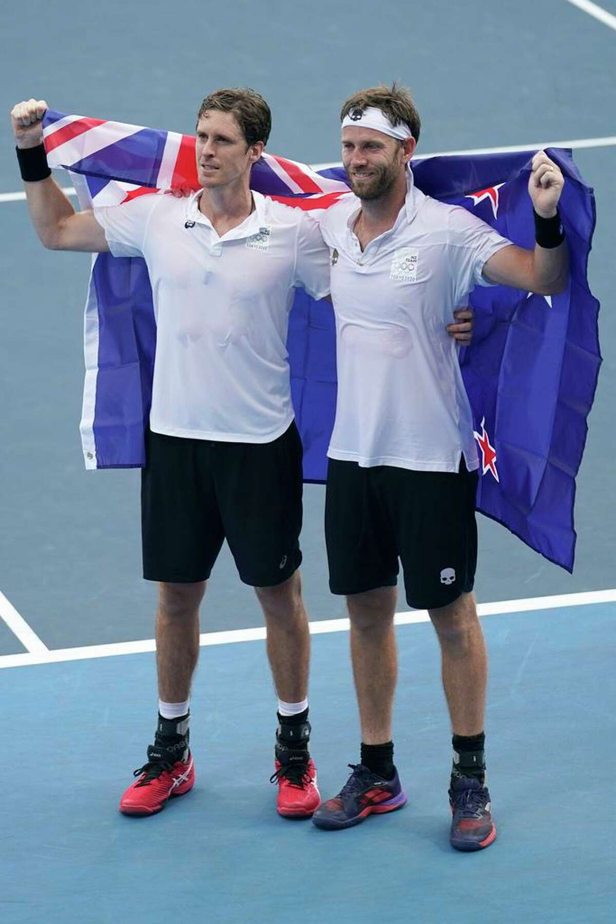 The New Zealand doubles team of Michael Venus, right, and Marcus Daniell celebrate with the flag of their country after defeating the team from the United States during the men's doubles bronze medal match of the tennis competition at the 2020 Summer Olympics, Friday, July 30, 2021, in Tokyo, Japan. Daniell practiced in Salisbury, Conn. during the pandemic.