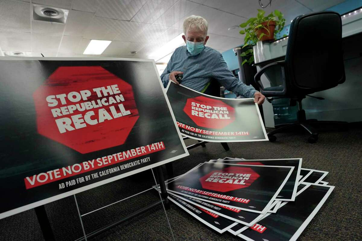 Volunteer Merle Canfield assembles anti-recall campaign signs at the Fresno County Democratic Party headquarters in Fresno last week.
