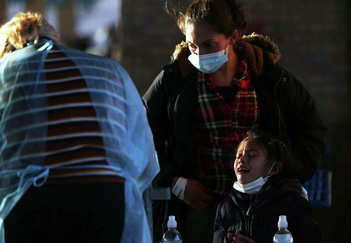 A young girl cries as her finger is pricked to test the blood for COVID-19 antibodies at the Brownsville, Texas bus station, Thursday, Feb. 25, 2021. Migrants, releases from U.S. Border Patrol custody after crossing the Rio Grande into the U.S., are typically dropped off at the station where charities are able to provide food, water and a place to rest before boarding a bus for their final destination. Under a new executive order by Gov. Greg Abbott, state troopers can pull over anyone whom they suspect is transporting migrants and send them back to their point of entry or origin.