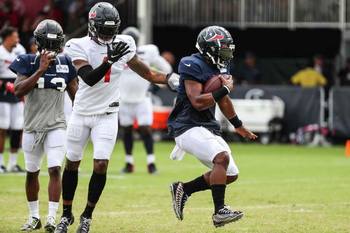 Houston Texans running back Mark Ingram (2) runs the ball past defensive back Lonnie Johnson (1) during an NFL training camp football practice Tuesday, Aug. 3, 2021, in Houston.