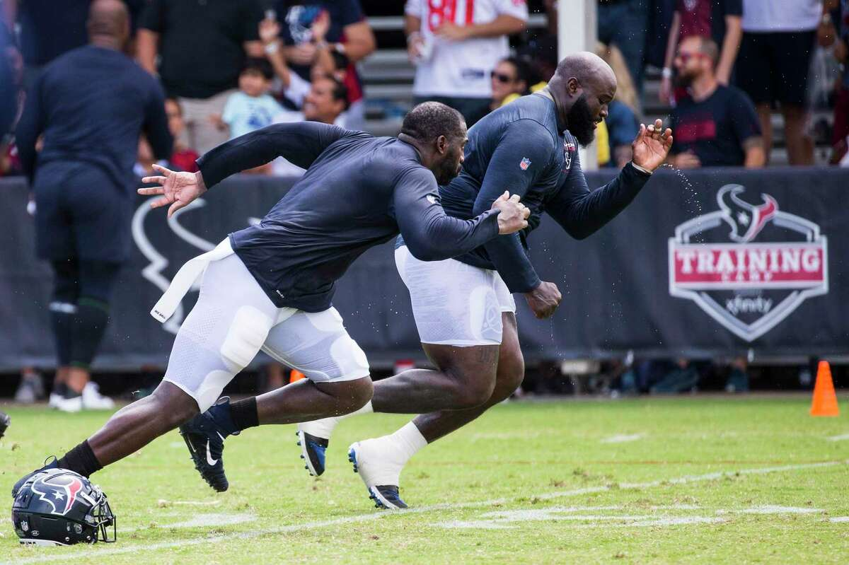 Houston Texans defensive end Whitney Mercilus (59) and defensive tackle Maliek Collins (97) run drills after an NFL training camp football practice Tuesday, Aug. 3, 2021, in Houston.