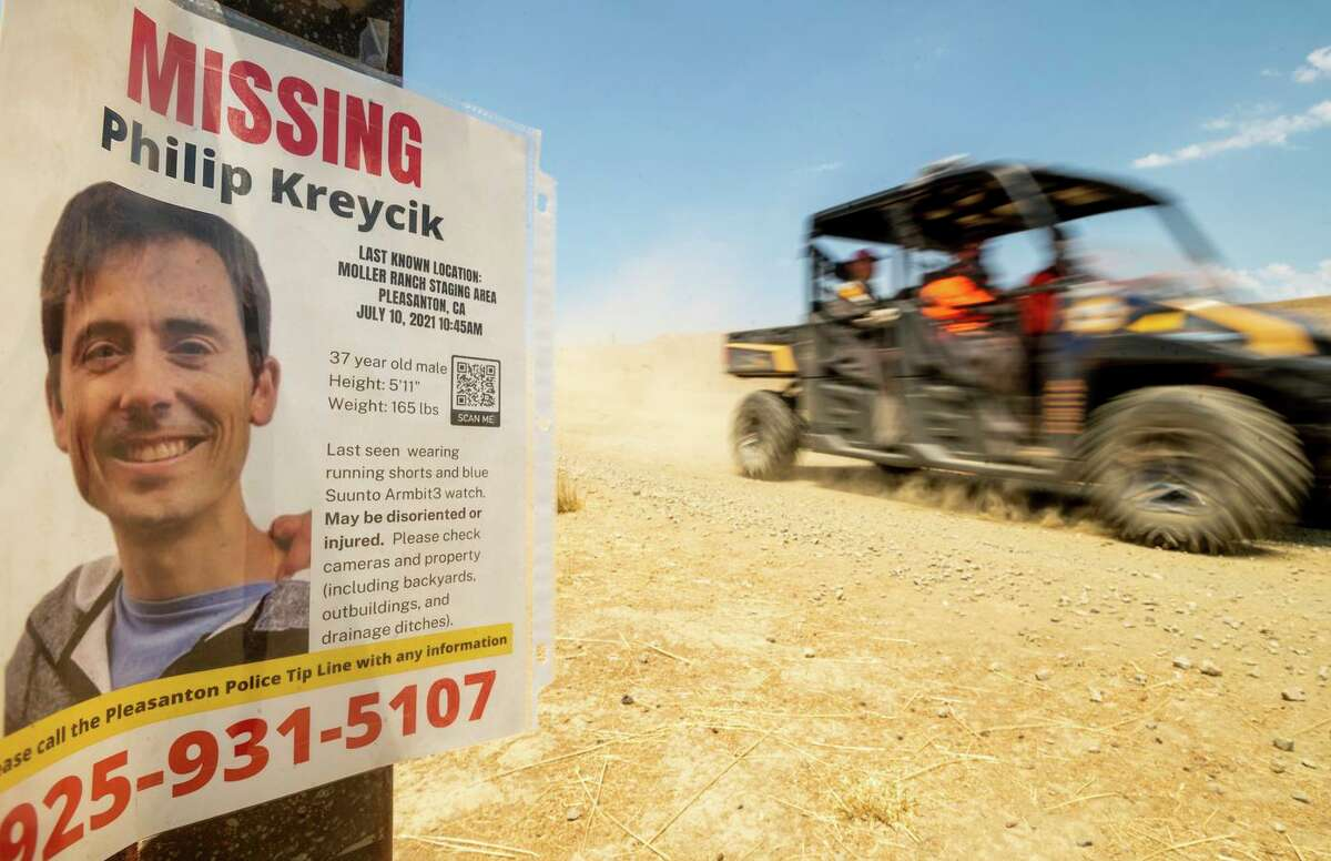 A search and rescue vehicle passes a poster for missing runner Philip Kreycik on Saturday.