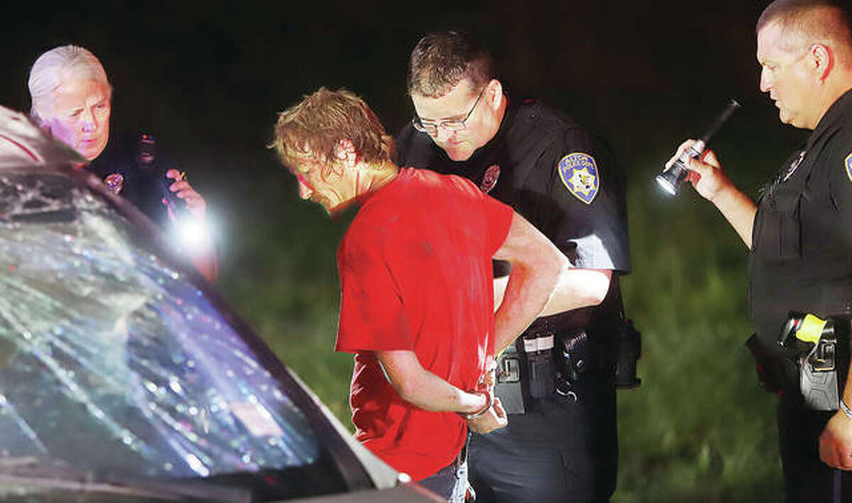 Police search the passenger of a rollover crash after taking him into custody Monday night on an outstanding warrant.