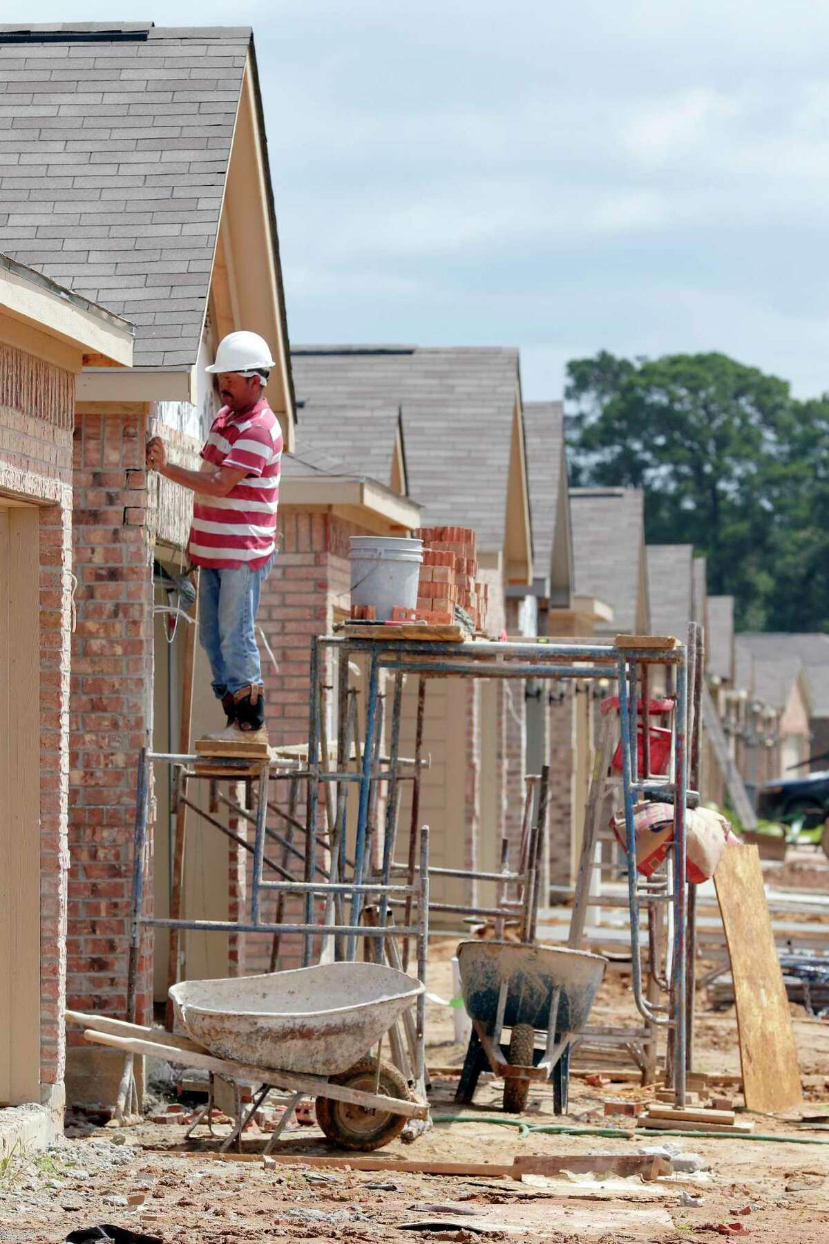 Construction workers lay bricks on the exteriors of new houses by LGI Homes. Homebuilders are dealing with the challenges of a red-hot housing market and rising material prices.