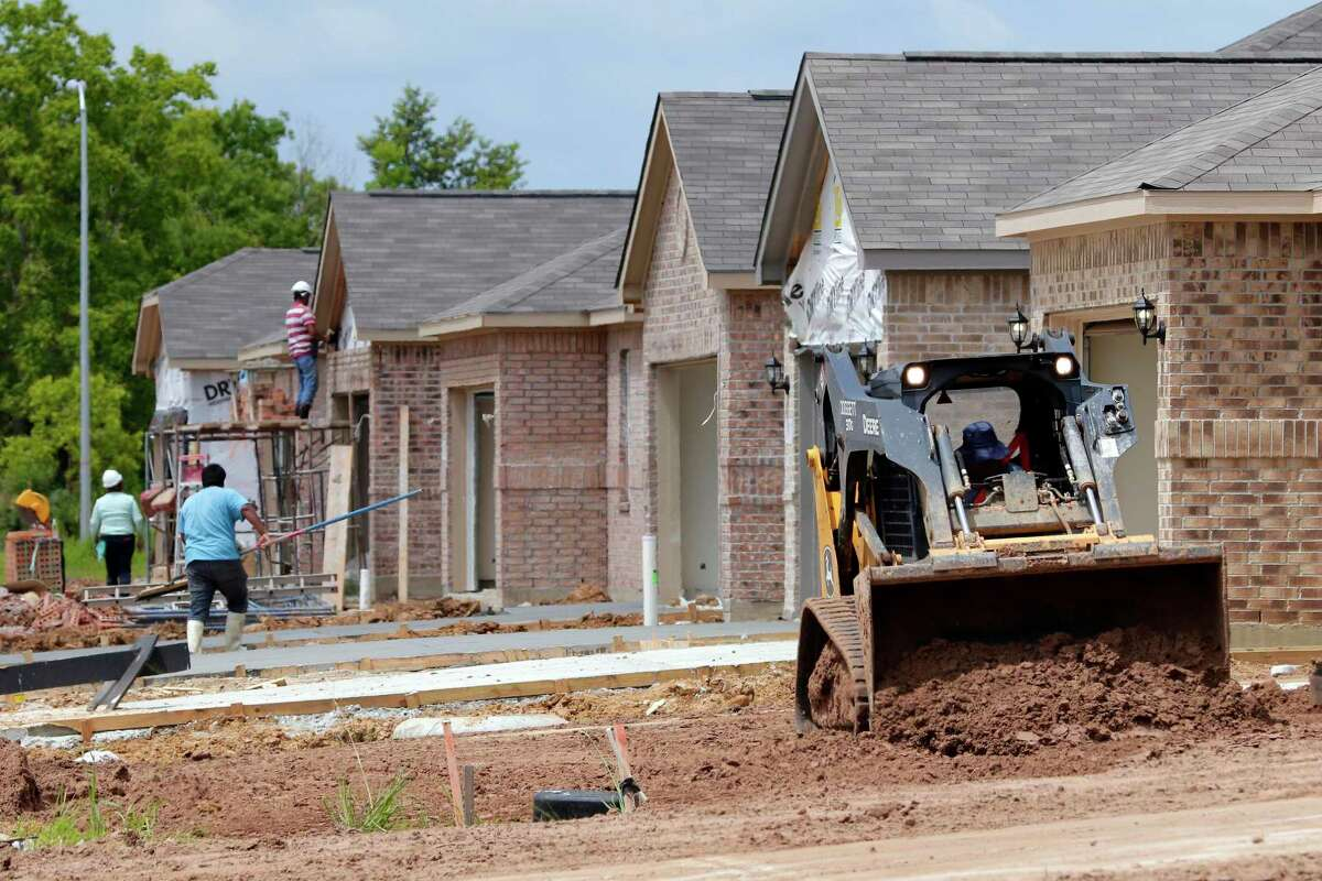Construction workers continue work on new housing construction of LGI Homes along Lost Lantern Drive in a new section of the Bauer Landing sub-division Thursday, June 3, 2021 in Hockley, TX. Homebuilders are dealing with the challenges of a red-hot housing market and rising material prices.