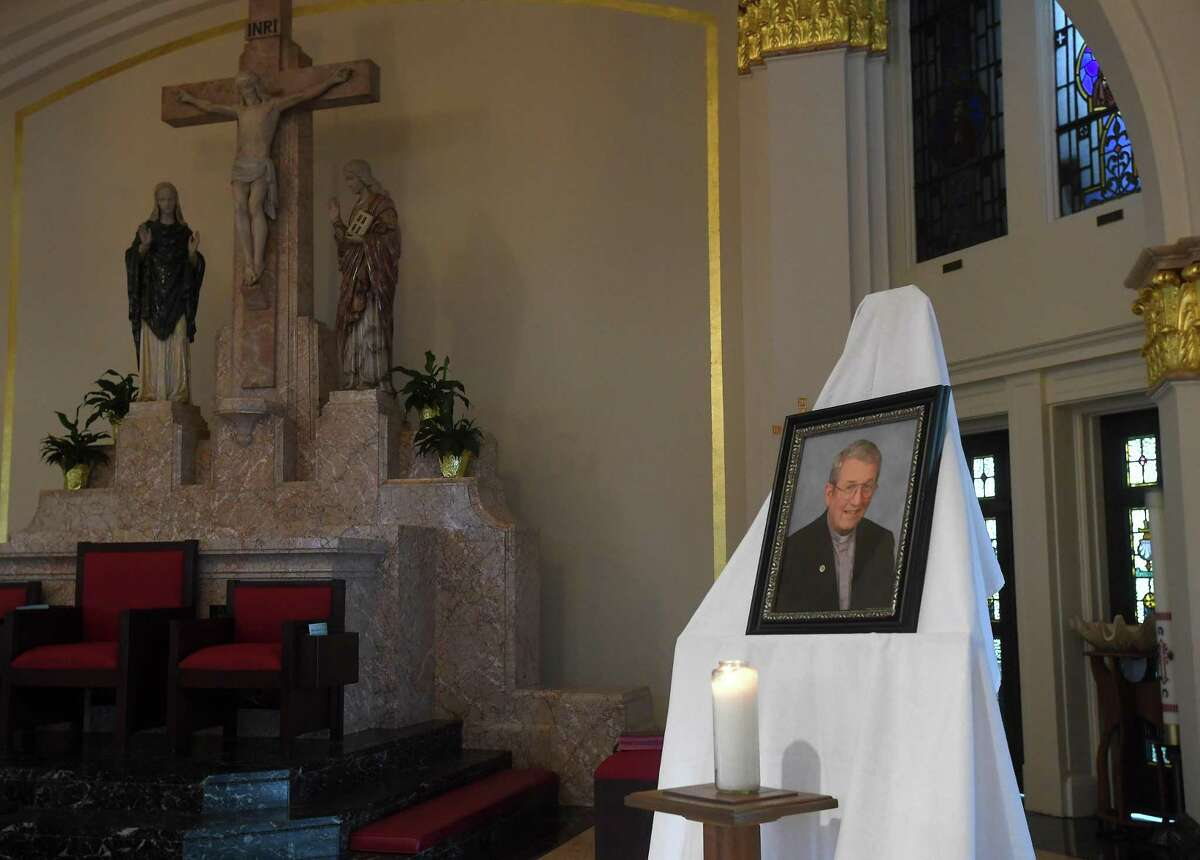 A candle sits in front of a photograph of Father William Manger on the altar at St. Anne Catholic Church in Beaumont, where a special mass was held in memorial of Fr. Manger, who passed away Monday. Photo made Tuesday, August 3, 2021 Kim Brent/The Enterprise