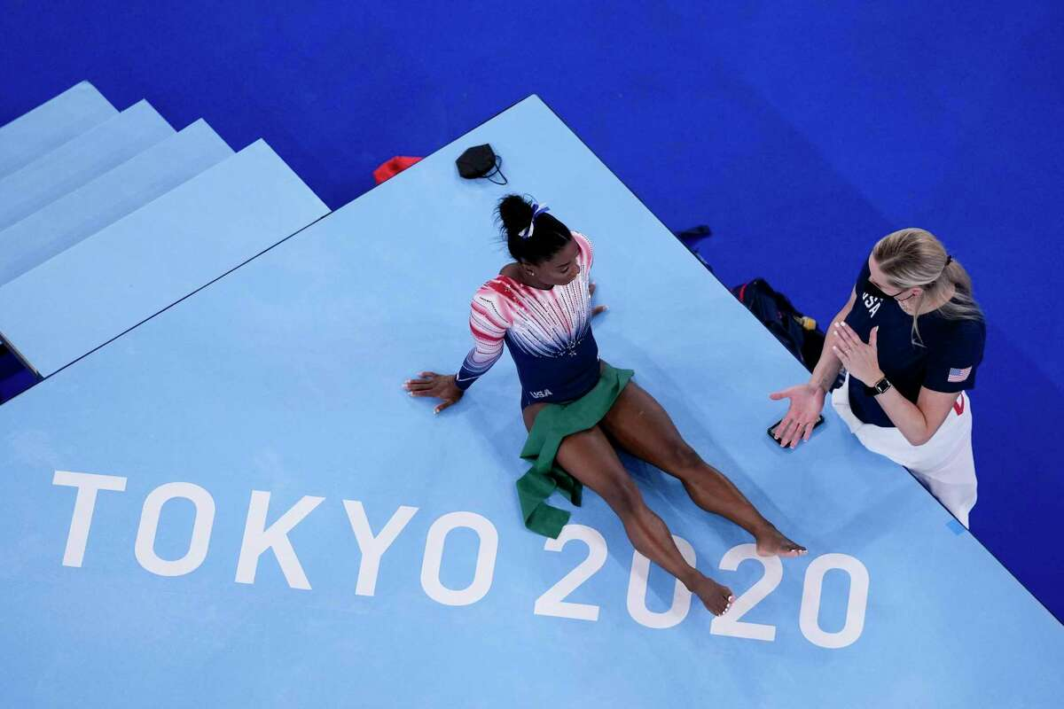 Simone Biles, of the United States, sits on the mat next to coach Cecile Landi during the warm up prior to the artistic gymnastics balance beam final at the 2020 Summer Olympics, Tuesday, Aug. 3, 2021, in Tokyo, Japan. (AP Photo/Morry Gash)