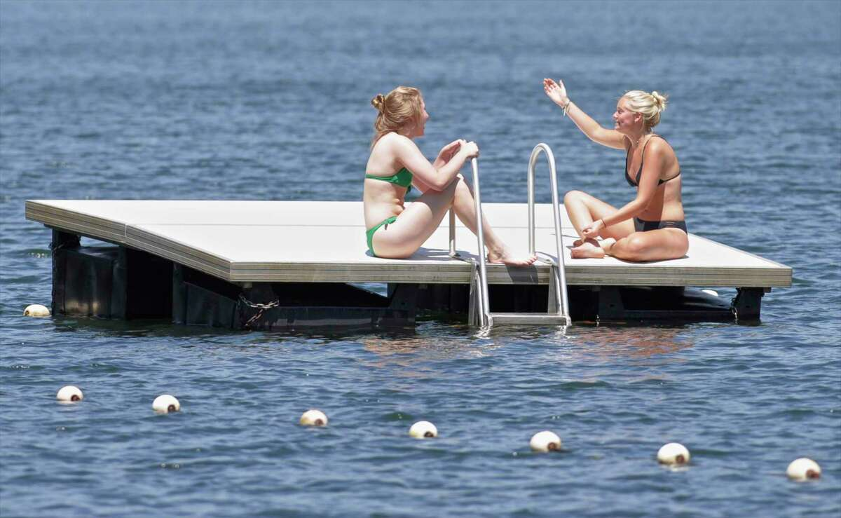 """Grace Federle, left, 16, and Lilly Hoeniger, 17, both of Washington, enjoy a day off in the sunshine on a float at the Washington Town Beach on Lake Waramaug in 2017. Litchfield County on Tuesday joined the rest of the state in having """"substantial"""" threats of COVID-19 spread."""