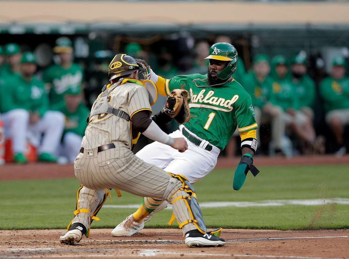 Josh Harrison (1) out at home on attempting to score after tagging up on a ball caught by Wil Myers (5) in the second inning as the Oakland Athletics played the San Diego Padres at the Coliseum in Oakland, Calif., on Tuesday, August 3, 2021.