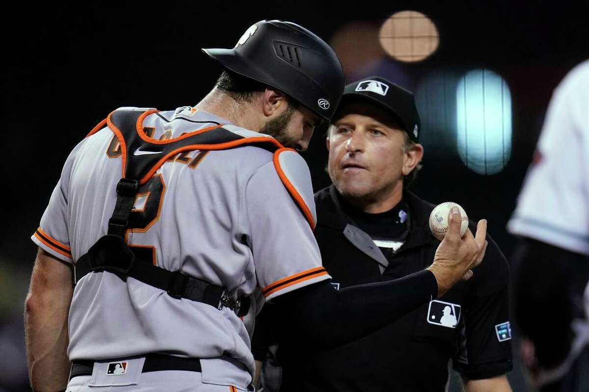 San Francisco Giants catcher Curt Casali, left, argues with umpire Chris Guccione after the umpire called him for an equipment violation during the second inning of the team's baseball game against the Arizona Diamondbacks, Tuesday, Aug. 3, 2021, in Phoenix. (AP Photo/Ross D. Franklin)